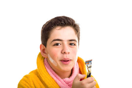 Caucasian smooth-skinned boy wears a yellow bathrobe with a pink towel around his neck: he has some patches on his face and smiling stares at the razor he used for shaving photo