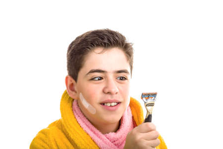 red skinned: Caucasian smooth-skinned boy wears a yellow bathrobe with a pink towel around his neck: he has some patches on his face and smiling stares with crossed eyes at the razor he used for shaving