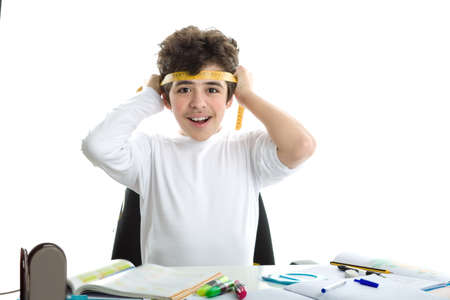 forehead: Before doing homework, handsome Caucasian smooth-skinned boy is smiling and tying around the forehead a yellow measure tape in a similar way as Japanese suicide bombers did during World War. blank icon in the foreground Stock Photo