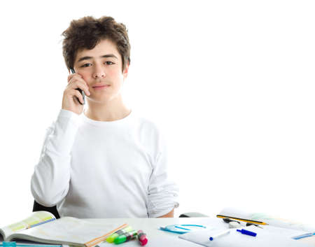 long sleeve: Handsome Caucasian smooth-skinned boy is talking on mobile phone while doing homework and wearing a white long sleeve t-shirt