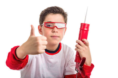 caulk: Caucasian smooth-skinned boy wearing red googles holds a red caulk gun with right hand smiling while he makes success sign with right hand Stock Photo