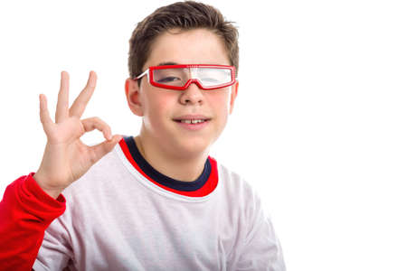 red skinned: Caucasian smooth-skinned boy wearing red googles smiles while he makes OK, all right, sign with right hand