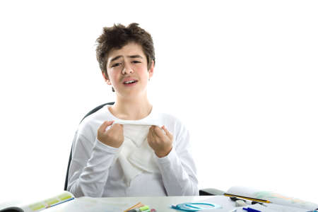 hankerchief: Cute Caucasian smooth-skinned boy sadly sitting in front of homework wearing a white long sleeve t-shirt and holding hankerchief to wipe tears Stock Photo