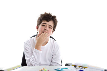dishevelled: Tired Caucasian smooth-skinned boy sits in front of homework wearing a white long sleeve t-shirt and yawns covering his mouth with right hand