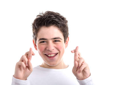 crossing fingers: Latin young boy with acne in a white long sleeve t-shirt smiles crossing fingers of both hands as superstitious  gesture to get luck