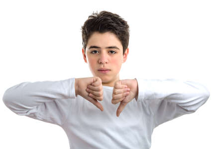 long sleeve: smooth-skinned Hispanic teen with acne skin in a white long sleeve t-shirt making dislike sign with both hands Stock Photo