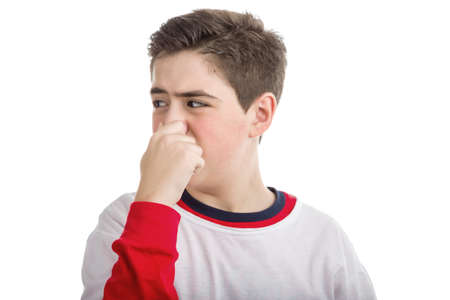 plugging: A cute Caucasian smooth-skinned boy is plugging his nose because of bad smell while wearing white t-shirt on a red one with longer sleeves