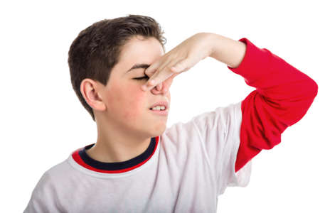 A cute Caucasian smooth-skinned boy is plugging his nose because of bad smell while wearing white t-shirt on a red one with longer sleeves photo