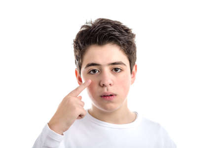white long sleeve: Worried Caucasian smooth-skinned boy in a white long sleeve t-shirt pointing to his eye with right  index finger Stock Photo