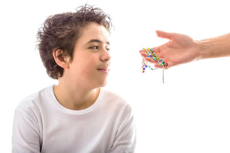 long sleeved: A happy Caucasian smooth-skinned boy wearing a white long sleeved t-shirt smiles receiving Rosary glass beads given by bare adult hands Stock Photo