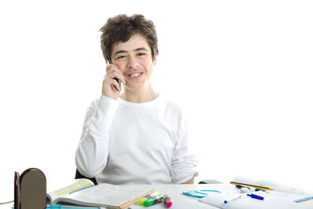Smiling handsome Caucasian smooth-skinned boy is talking on cell phone while doing homework and wearing a white long sleeve t-shirt photo