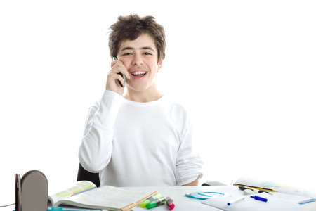 white long sleeve: Smiling handsome Caucasian smooth-skinned boy is talking on mobile phone while doing homework and wearing a white long sleeve t-shirt Stock Photo