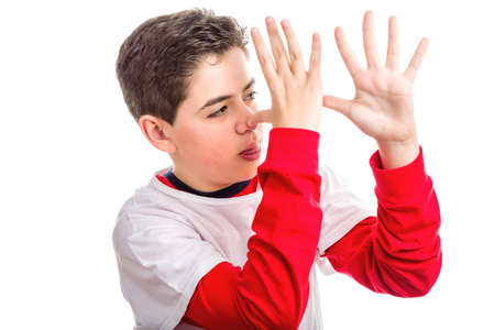 long sleeved: Caucasian smooth-skinned boy wearing red long sleeved shirt thumbs his nose from left to right with both hands showing profile