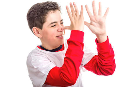 banter: Caucasian smooth-skinned boy wearing red long sleeved shirt thumbs his nose from left to right with both hands showing profile