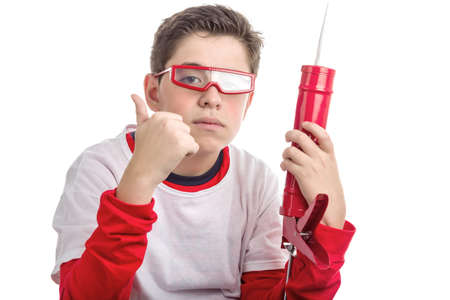 caulk: Caucasian smooth-skinned boy wearing red googles holds a red caulk gun with right hand while he makes success sign with right hand: he looks a calm and confident professional Stock Photo