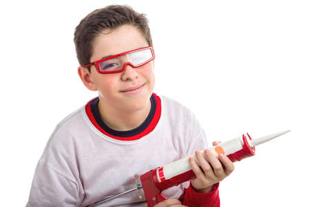 caulk: Caucasian smooth-skinned boy wears red googles with clear lenses and with right hand smiling  he holds a red caulking gun