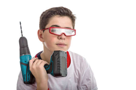 red skinned: Caucasian smooth-skinned boy wears red googles with clear lenses and with right hand he holds a green cordless drill