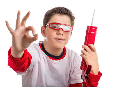 caulk: Caucasian smooth-skinned boy wearing red goggles holds a red caulk gun with right hand smiling while he makes success sign with right hand