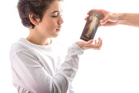 merciful: A happy Caucasian smooth-skinned boy in a white long sleeves t-shirt smiles receiving with right hand a Merciful Jesus wood icon given by an adult hand