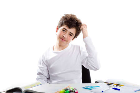 interdict: Thoughtfully and interdict Caucasian teenager boy smiling scratches his head with left hand while doing homework