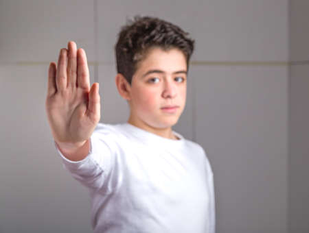 dislike it: Blurred Caucasian smooth-skinned teen in a white long sleeve t-shirt making Talk to the hand gesture with right hand Stock Photo
