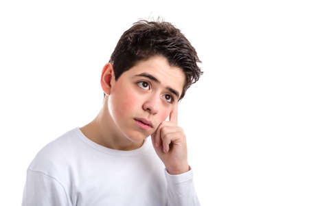 Worried Caucasian smooth-skinned teenager skin in a white long sleeve t-shirt broods holding his head with index finger of left hand