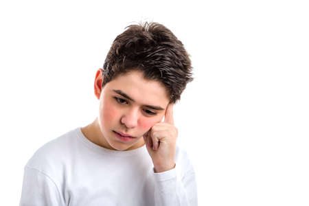 cogitate: Worried smooth-skinned Caucasian teenager in a white long sleeve t-shirt meditates  holding his head with index finger of left hand