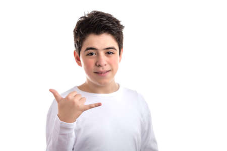 hang loose: Smooth-skinned Caucasian boy wearing a white long sleeve t-shirt smiles doing Hawaiian shaka, hang loose, gesture with hand