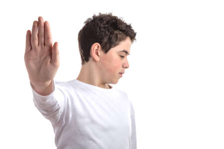 long sleeve: Blurred Caucasian smooth-skinned teen in a white long sleeve t-shirt smiles making Talk to the hand gesture with right hand Stock Photo
