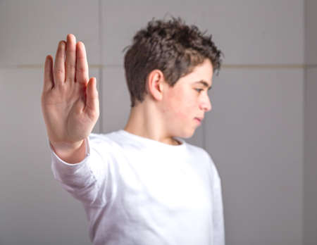 dislike it: Blurred Caucasian smooth-skinned teen in a white long sleeve t-shirt smiles making Talk to the hand gesture with right hand Stock Photo
