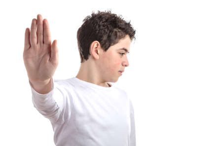 dislike it: Caucasian smooth-skinned teen in a white long sleeve t-shirt smiles making Talk to the hand gesture with right hand Stock Photo