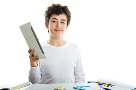 white long sleeve: Calm and confident Caucasian boy wearing a white long sleeve t-shirt is holding a tablet computer on homework Stock Photo
