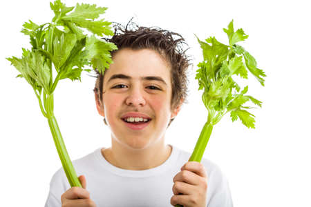 long sleeved: Handsome hispanic boy in white long sleeved t-shirt is smiling while holding green celery sticks with both hands