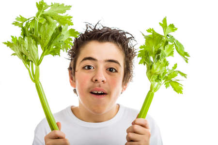 sleeved: Handsome hispanic boy in white long sleeved t-shirt is smiling while holding green celery sticks with both hands