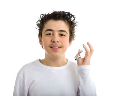 long sleeved: Handsome hispanic boy in white long sleeved t-shirt is holding a lightbulb in the same way as hes going to listen to it Stock Photo