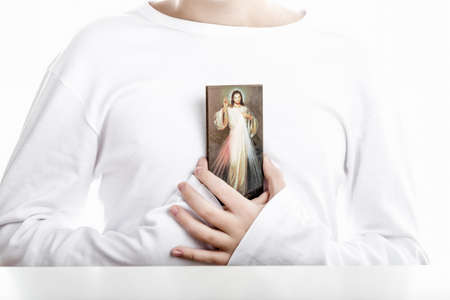 long sleeved: A Caucasian boy holds resting on his chest a picture of Merciful Jesus. He wears long sleeved shirt