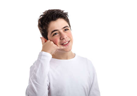 long sleeve: Caucasian boy wearing a white long sleeve t-shirt smiles making a phone call gesture with right hand Stock Photo