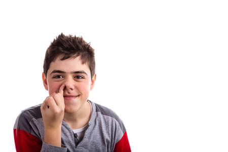 dedo meÑique: Muchacho caucásico en pijama rojo y gris sonríe burlas y poniendo el dedo meñique en la nariz