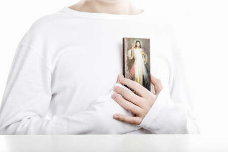 sleeved: A Caucasian boy holds resting on his chest a picture of Merciful Jesus. He wears long sleeved shirt