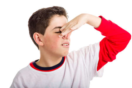 A cute Caucasian boy is plugging his nose because of bad smell while wearing white t-shirt on a red one with longer sleeves photo