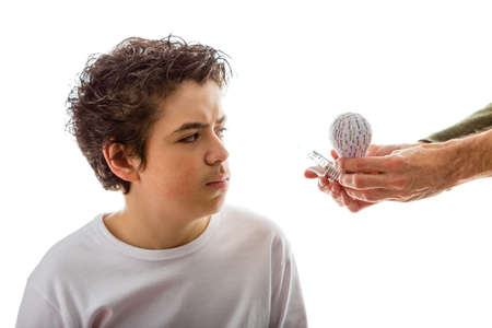 rapid prototyping: A Caucasian boy takes a puzzled look to 3D prototype and real lightbulb that adult hand is giving to him from his left side Stock Photo