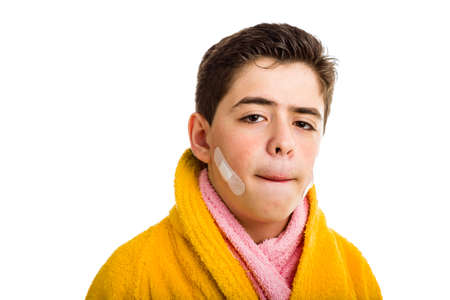 reddening: A Caucasian boy wears a yellow bathrobe with a pink towel: he has some patches on his face after shaving but he looks calm and confident while stretching the skin above the lip to check cuts Stock Photo