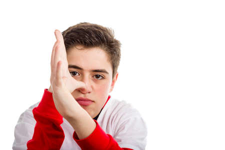 derision: A Caucasian boy wearing red long sleeved shirt thumbs his nose with both hands
