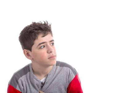 m�lancolie: Gar�on de race blanche en pyjama rouge et gris perdu dans ses pens�es avec un regard r�veur et m�lancolique Banque d'images