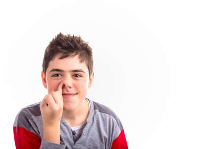 nose picking: Caucasian boy in red and grey pajamas child picks his nose painting a quizzical smile