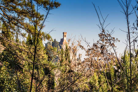 crenellated tower: A  medieval crenellated clock tower stands on a peak overlooking the valley of a village and a country of farmland, bushes, cypresses and other tress among braches in the mist of a sunny winter day