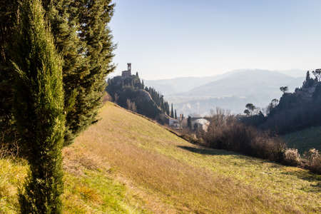 crenellated: A  medieval crenellated clock tower stands on a peak overlooking the valley of a village and a country of farmland, bushes, cypresses and other tress in the mist of a sunny winter day Editorial