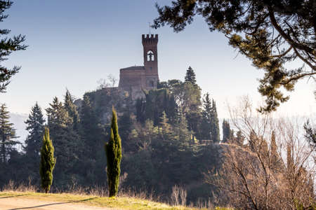 bulwark: A  medieval crenellated clock tower stands on a peak overlooking the valley of a country of farmland, bushes, cypresses and other tress in the mist of a sunny winter day
