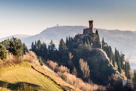 crenellated: A  medieval crenellated clock tower stands on a peak overlooking the valley of a country of farmland, bushes, cypresses and other tress in the mist of a sunny winter day
