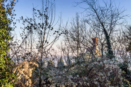 crenellated: A  medieval crenellated clock tower stands on a peak overlooking the valley of a village and a country of farmland, bushes, cypresses and other tress among braches in the mist of a sunny winter day